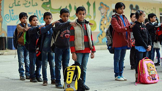 Schülerinnen und Schüler stehen in Reihen vor einer Schule in Bengasi.