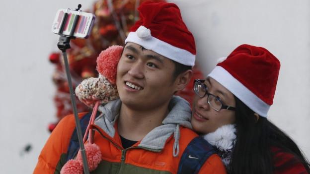 Zu sehen ist ein junges Paar im Sankt-Nikolaus-Look, das in einer katholischen Kirche in Peking eine Selfie-Aufnahme macht.