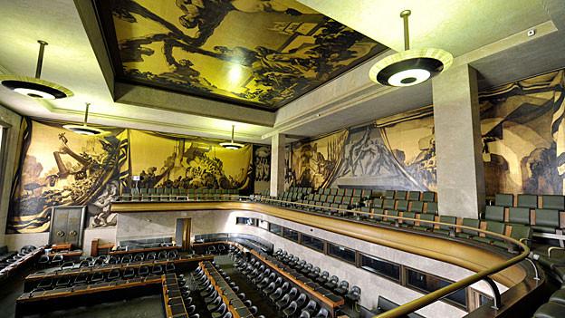 Blick in den Ratssaal im Palais des Nations. Wände und Decke sind mit Gemälden geschmückt.