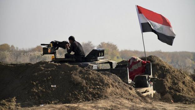 Irakische Sicherheitskräfte postieren am 27. Dezember 2015 eine Flagge in der Stadt Ramadi.