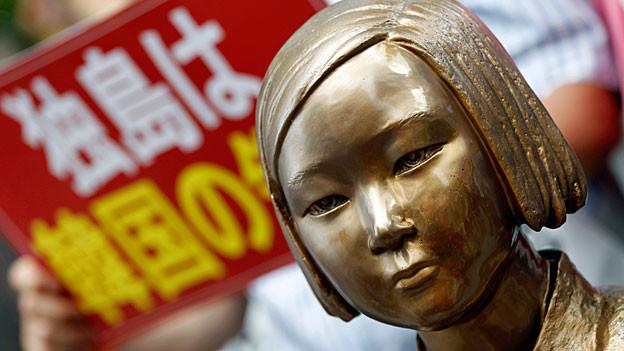 Die Skulptur einer jungen südkoreanischen Frau steht vor der japanischen Botschaft in Seoul.