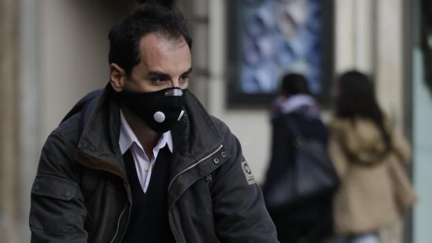 Ein Velofahrer in Rom schützt sich mit Maske vor dem Smog (24. Dezember 2015).