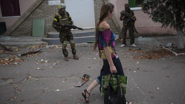 Eine Frau läuft an bewaffneten Soldaten vorbei.
