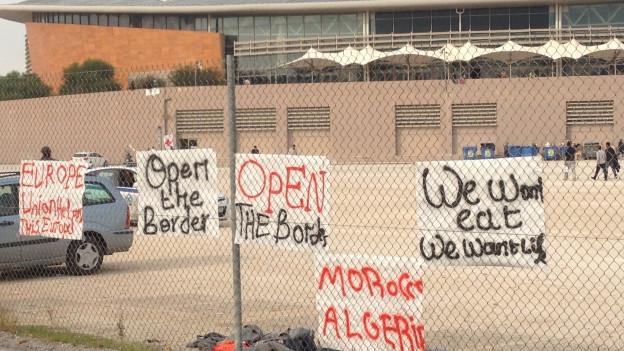 Abgewiesene Flüchtlinge protestieren mit Plakaten bei der umfunktionierten olympischen Taekwondo-Halle in Athen.