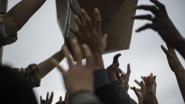 Flüchtlinge in Calais strecken ihre Arme aus für Hilfspakete.