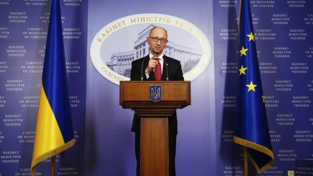 Der ukrainische Premier Arseni Jaseniuk spricht an einem Rednerpult, links von ihm hängt eine ukrainische, rechts von ihm eine europäische Flagge.