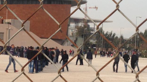Blick durch Maschendrahtzaun auf Menschen vor Sportstadion