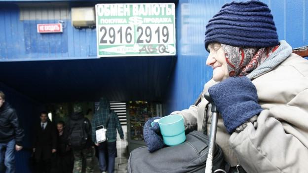 Zu sehen ist eine alte Frau, die in Moskau um Geld bettelt.