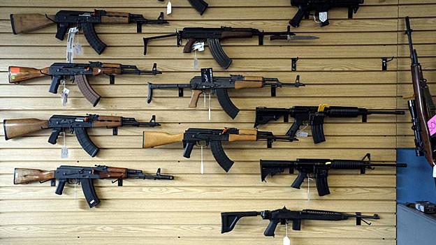 Im Schaufenster eines Waffengeschäfts sind halbautomatische und automatische Waffen ausgestellt.