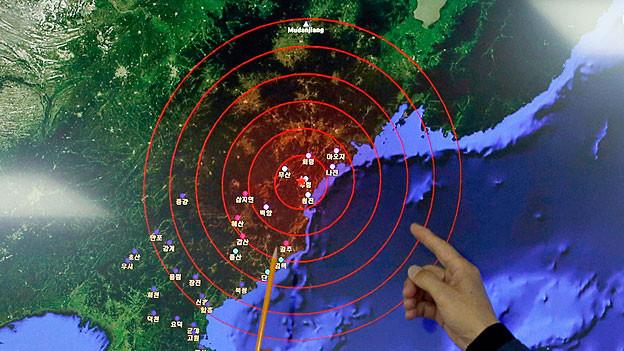 Ein südkoreanischer Meteorologe zeigt auf einer Landkarte die Stelle, an der Atomtest stattgefunden haben soll.
