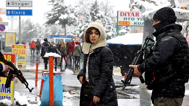 Eine Kurdin steht auf einer Strasse der Stadt Diyarbakir zwischen zwei bewaffneten Polizisten
