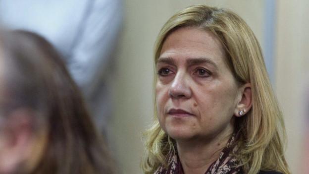 Nahaufnahme von Cristina de Burbón, sie sitzt im Gerichtssaal und blickt an der Kamera vorbei nach links.