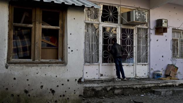 Mann vor zerschossenem Haus schaut durch ein Fenster.