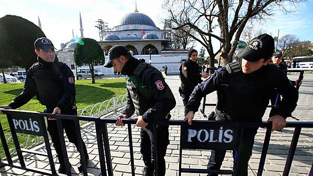 Drei türkische Polizisten montieren eine Absperrung; im Hintergrund die blaue Moschee.