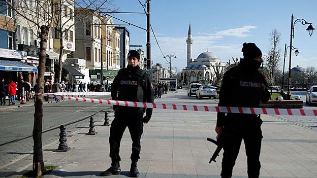 Türkische Polizisten sichern den Ort, an dem das Attentat stattfand; im Hintergrund die blaue Moschee.