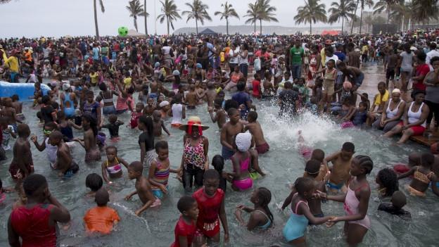 Viele Menschen stehen im flachen Wasser an einem Strand.