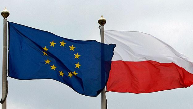 Eine EU- und eine polnische Flagge wehen im Wind.