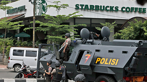 Polizeikräfte stehen neben einem gepanzerten Fahrzeug vor dem Starbucks-Kaffe, wo einer der Anschläge stattgefunden hat.
