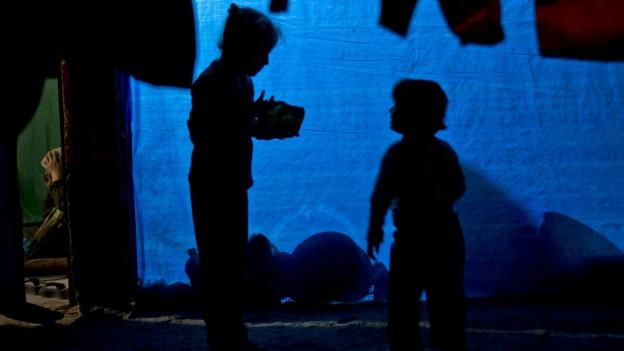 Syrische Flüchtlingskinder sprechen nach Erhalt von Lebensmittelrationen in einem Camp in Suruc miteinander.