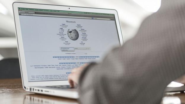 Ein Mann sucht etwas auf Wikipedia