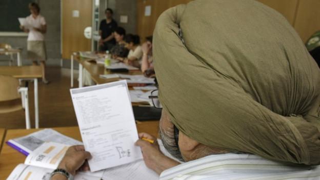 Ein Inder nimmt an einem Deutschkurs für Ausländer an der Volkshochschule in Stuttgart teil.