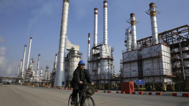 Auf dem Foto fährt ein iranischer Ölarbeiter an einer Teheraner Ölraffinerie südlich der Hauptstadt Teheran vorbei.