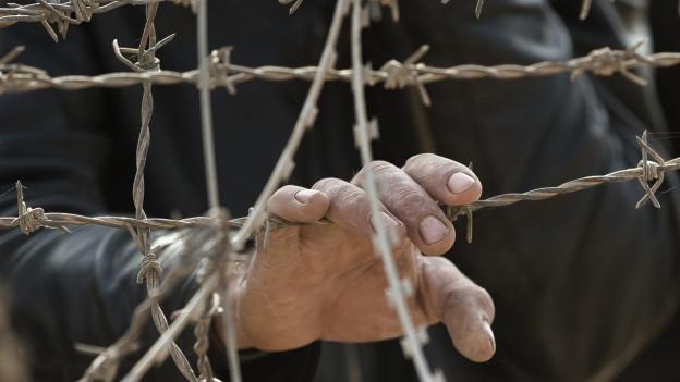 Ein syrischer Kurde hält seine Hand an den Stacheldrahtzaun.