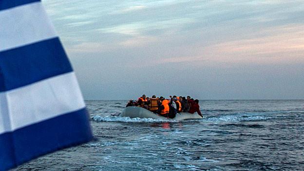 Hinter einer im Wind wehenden griechischen Flagge sieht man ein Boot mit Flüchtlingen auf dem Meer.