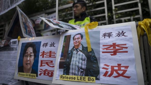 Plakate mit Fotos der vermissten Buchhändler.