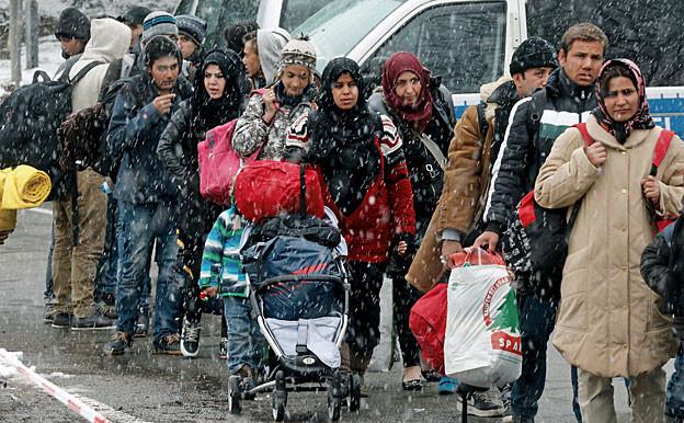 Eine Gruppe Flüchtlinge, Männer, Frauen Kinder, sind bei starkem Schneefall unterwegs.