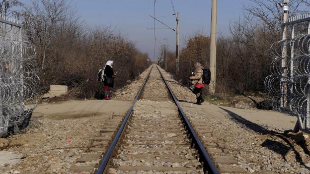 In der Mitte ein Bahngeleis, auf jeder Seite steht eine Frau. Hinter den beiden jeweils Grenzzäune mit Stacheldraht.