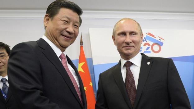 Chinas Präsident Xi Jinping lächelt mit dem russischen Präsidenten Wladimir Putin zusammen in die Kamera. Hier an einem Treffen im Jahr 2013 in St. Petersburg.