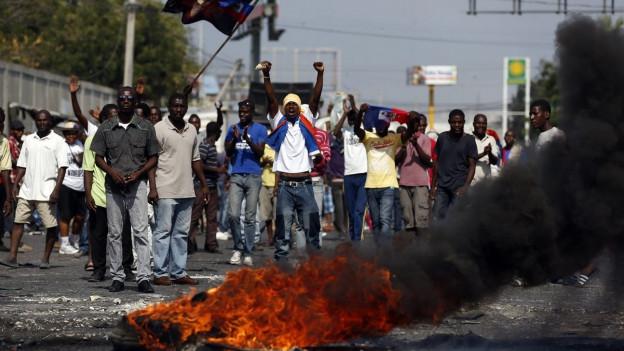 Demonstranten schreien Parolen hinter brennenden Reifen während einer Protestaktion in Port-au-Prince, Haiti.