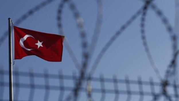 Auf dem Bild ist die türkische Flagge hinter Stacheldrahtzaun zu sehen.