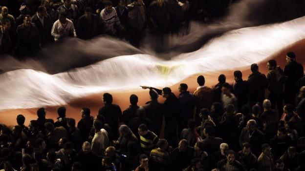 Eine Menschenmenge demonstriert 2011 auf dem Tahrir in Kairo mit einer riesigen Ägyptenfahne.