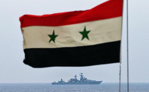 Eine syrische Flagge weht im Wind; darunter ist in der Ferne ein syrisches Kriegsschiff auf dem Mittelmeer zu sehen.