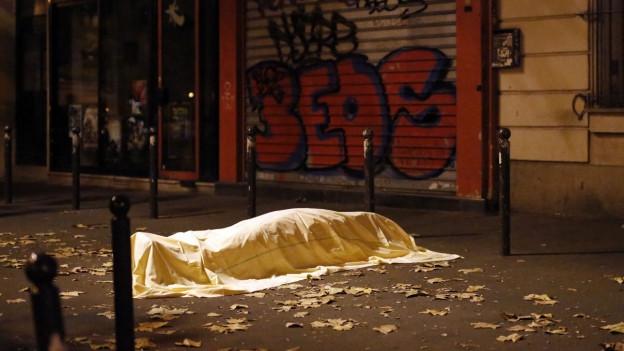 Eine Leiche liegt nach den Anschlägen von Paris unter einem Tuch am Boden.
