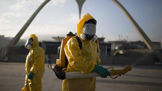 Rio de Janeiro: Ein Mann in einem Schutzanzug sprüht grosse Mengen von Insektenmittel in die Luft.