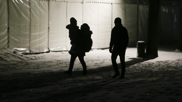 Eine Flüchtlingsfamilie kommt an einem kalten und schneereichen frühen Januarmorgen bei der zentralen Registrierungsstelle für Flüchtlinge und Asylsuchende in Berlin an.