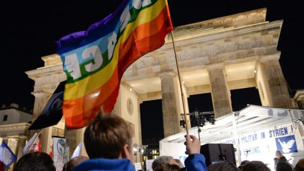Ein Demonstrant hält eine Friedensflagge bei einem Protest gegen die deutsche Militäraktion in Syrien in Berlin in die Höhe.