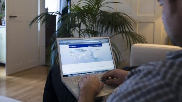 Ein Mann loggt sich am Laptop bei Facebook ein.
