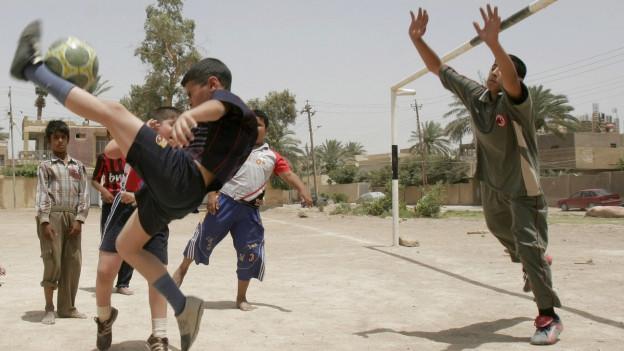 Irakische Kinder spielen draussen Fussball zusammen