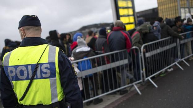 Schwedische Polizisten beobachten neu angekommene Flüchtlinge im November 2015 außerhalb von Malmö.