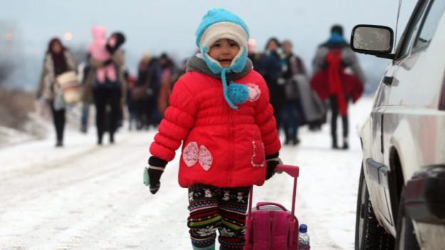 Flüchtlingskind alleine auf der Strasse, zieht ein Koffer, Schnee.