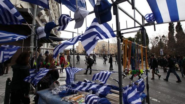 Das Bild zeigt einen Stand mit vielen Griechenland-Flaggen, dahinter Menschen auf einer für den Verkehr gesperrten Strasse.