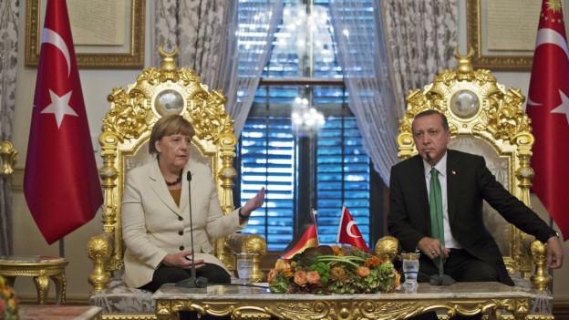 Angela Merkel sitzt in einem prachtvollen Raum neben Recep Erdogan.