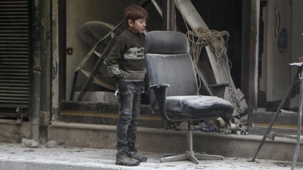 Junge vor einem zerbombten Haus.