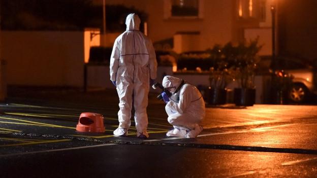 Zwei Personen in Schutzanzügen am Tatort.
