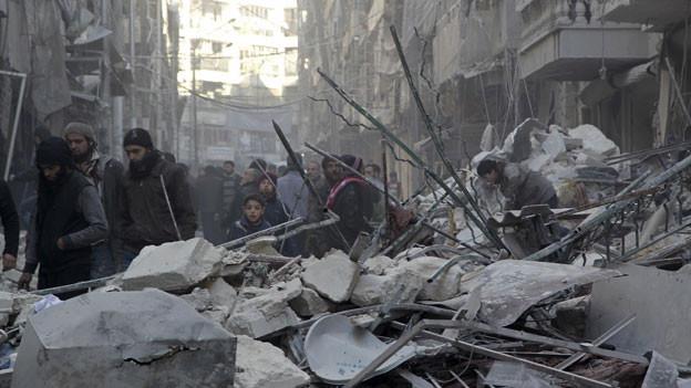 Die Bewohner der Stadt Al-Shaar in der Nähe von Aleppo betrachten die Schäden nach Luftangriffen durch pro-syrische Regierungstruppen.