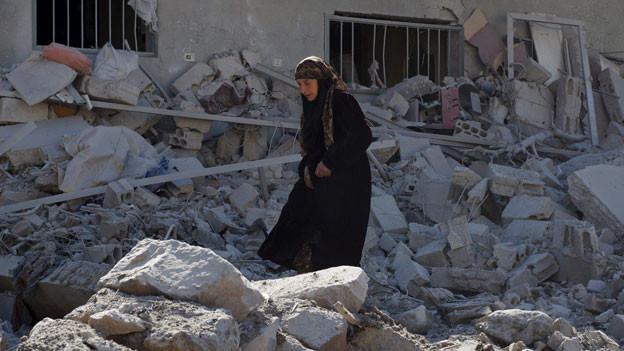 Eine Frau sucht sich ihren Weg durch die Trümmer der zerstörten Gebäude in der syrischen Stadt Dale am 12. Februar 2016.